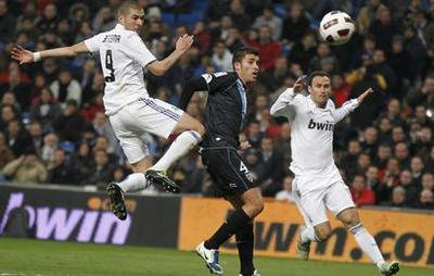 Real Madrid's Benzema looks at the ball after shooting to score against Malaga during their Spanish first division soccer match in Madrid